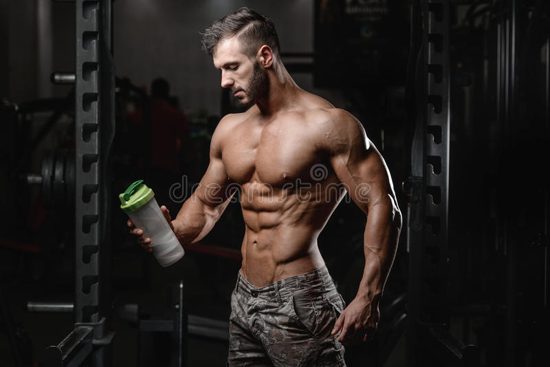 Handsome athletic fitness man holding a shaker and posing gym royalty free stock images