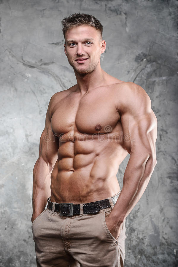 Handsome athletic fitness muscular man posing on a gray background in studio royalty free stock images