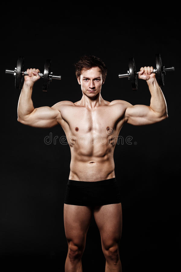 Handsome athletic man with dumbbells confidently looking forward stock photography