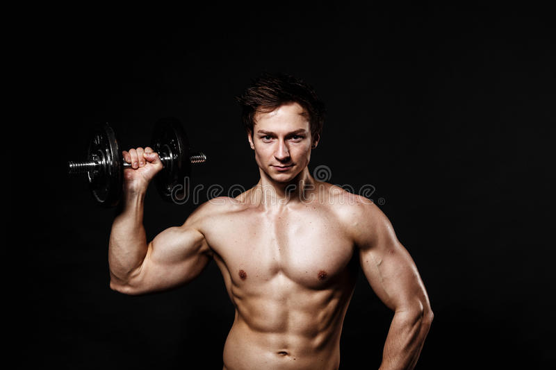 Handsome athletic man with dumbbells confidently looking forward stock photo