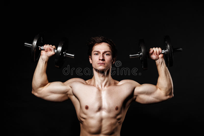 Handsome athletic man with dumbbells confidently looking forward stock photos