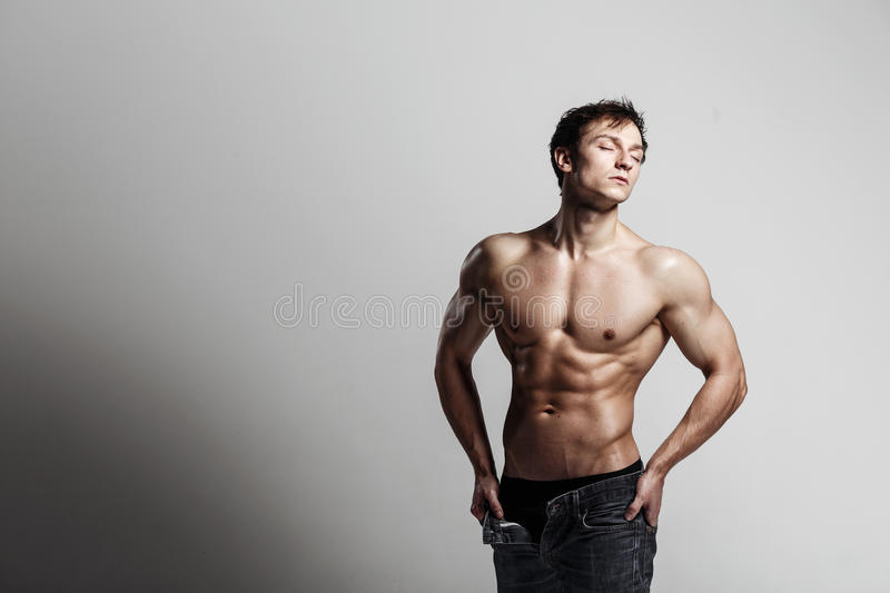Handsome athletic man looking at side in unbuttoned jeans. Strong bodybuilder with six pack, perfect royalty free stock image
