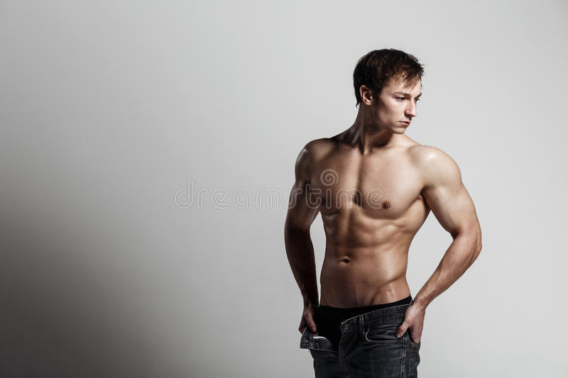 Handsome athletic man looking at side in unbuttoned jeans. Strong bodybuilder with six pack, perfect stock photos