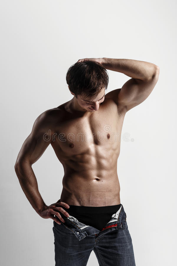 Handsome athletic man looking at side in unbuttoned jeans. Strong bodybuilder with six pack, perfect royalty free stock images