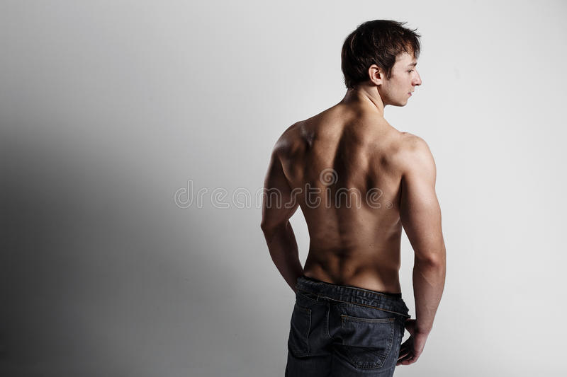 Handsome athletic man looking at side in unbuttoned jeans. Strong bodybuilder with six pack, perfect stock photography