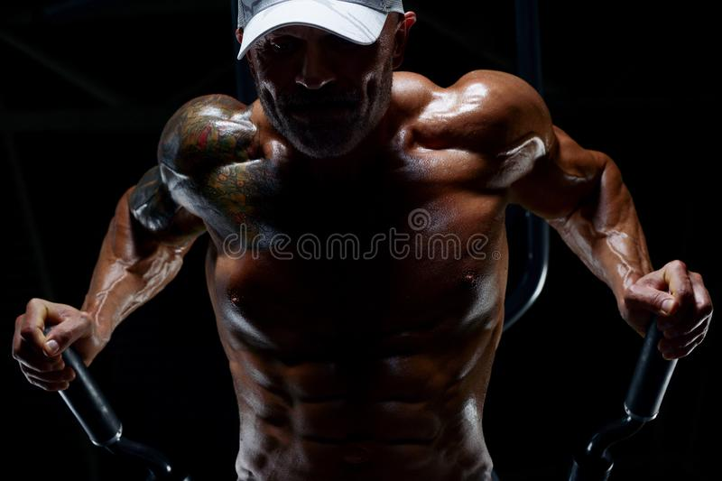 Handsome athletic men pumping up muscles push-ups on uneven bars workout fitness exercises and bodybuilding concept background -. Handsome athletic man pumping stock photo