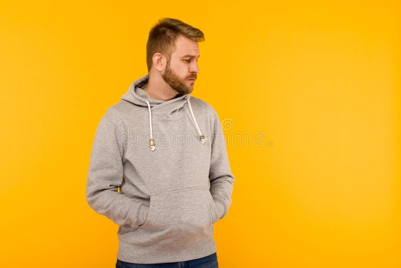 Handsome attractive European man in gray hoodie on yellow background royalty free stock images