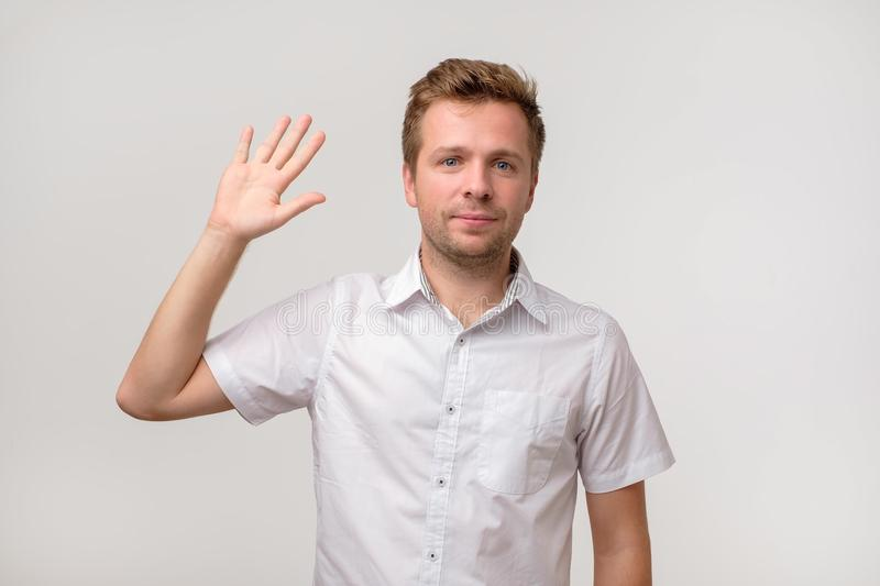 Handsome attractive european man waiving hand in hello gesture while smiling cheerfully. royalty free stock photography