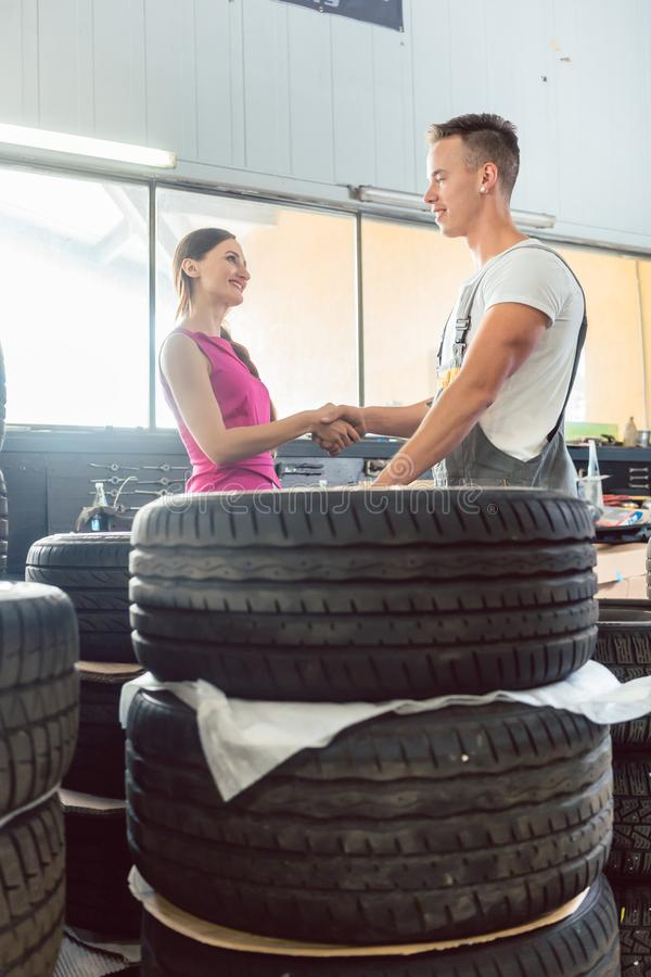 Handsome auto mechanic helping a customer to choose from various tires royalty free stock photos