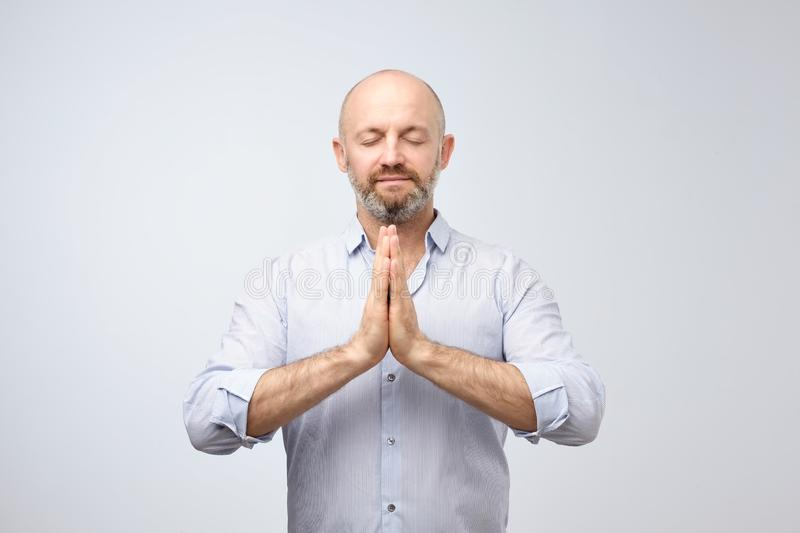 Handsome bald man with bristle keeping eyes closed while meditating, feeling relaxed, calm, peaceful royalty free stock photo