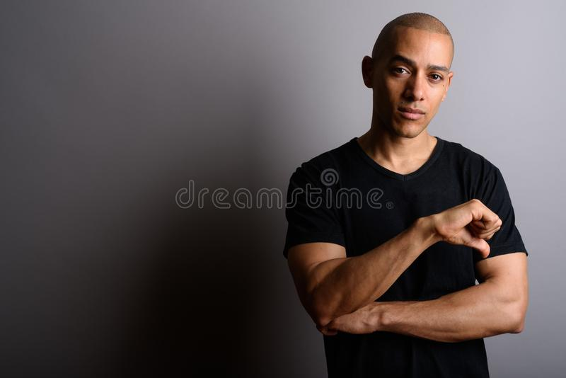 Handsome bald man giving thumb down against gray background royalty free stock image