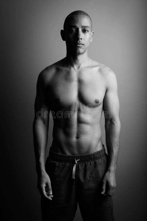 Handsome bald man shirtless in black and white stock photos