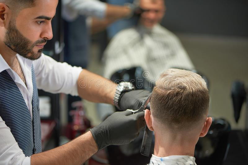 Handsome barber in black gloves cutting haircut of man using scissors. stock image