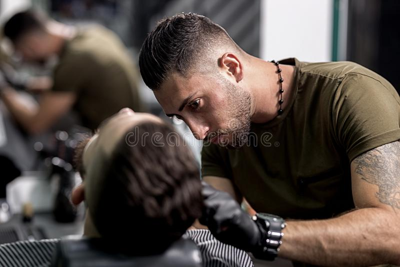 Handsome barber in black gloves trims a beard of stylish man at a barbershop stock images