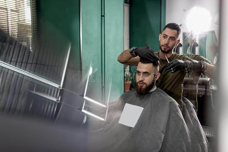 Handsome barber cuts with scissors hair of stylish bearded man at a barbershop stock photos