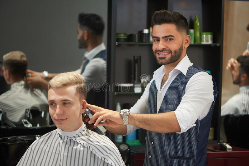 Handsome barber trimming client`s haircut, looking at camera and smiling. stock images