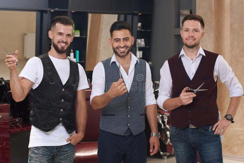 Handsome barbers posing with scissors and smiling. stock image