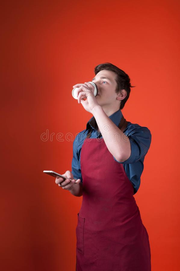 Handsome barista in burgundy apron holding smartphone and drinking coffee. On coral color background royalty free stock photography