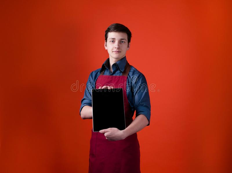 Handsome barista in burgundy apron looking at camera and showing digital tablet with blank screen. On orange background with copy space stock photos