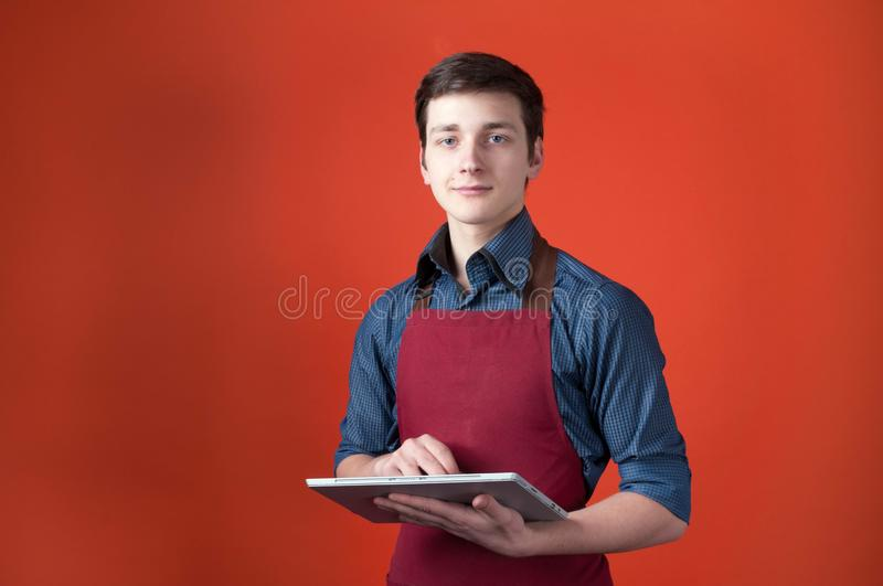 Handsome barista in burgundy apron looking at camera and using digital tablet in front of coral color background. With copy space royalty free stock images