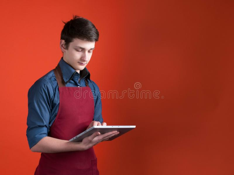Handsome barista in burgundy apron using digital tablet on coral color background. Side view of handsome barista in burgundy apron using digital tablet on coral royalty free stock images