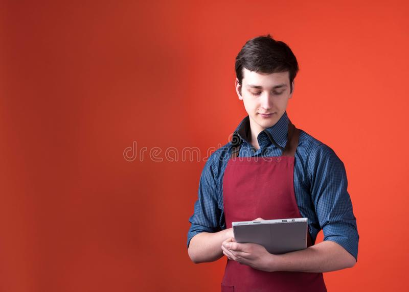 Barista with dark hair in burgundy apron holding and looking at digital tablet on orange background. Handsome barista with dark hair in burgundy apron holding stock images