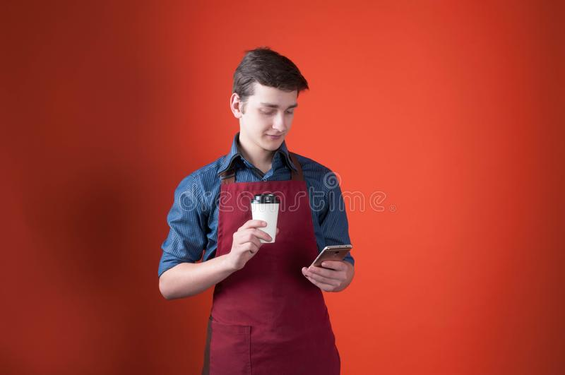Barista with dark hair in burgundy apron holding paper cup with coffee and using smartphone on orange background. Handsome barista with dark hair in burgundy royalty free stock images
