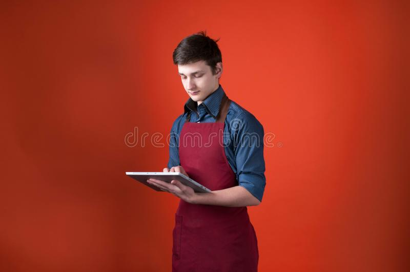 Handsome barista with dark hair in burgundy apron using digital tablet on orange background. Side view of handsome barista with dark hair in burgundy apron using royalty free stock photo