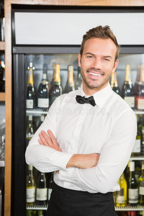 Handsome barman with arms folded. In a pub royalty free stock photos