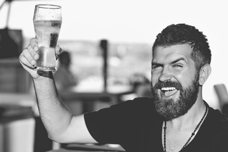 Handsome barman holding a pint of beer. Man holds glass of beer. Enjoy in pub. Beer time. Handsome barman holding a pint of beer. Man holds glass of beer. Enjoy royalty free stock photo