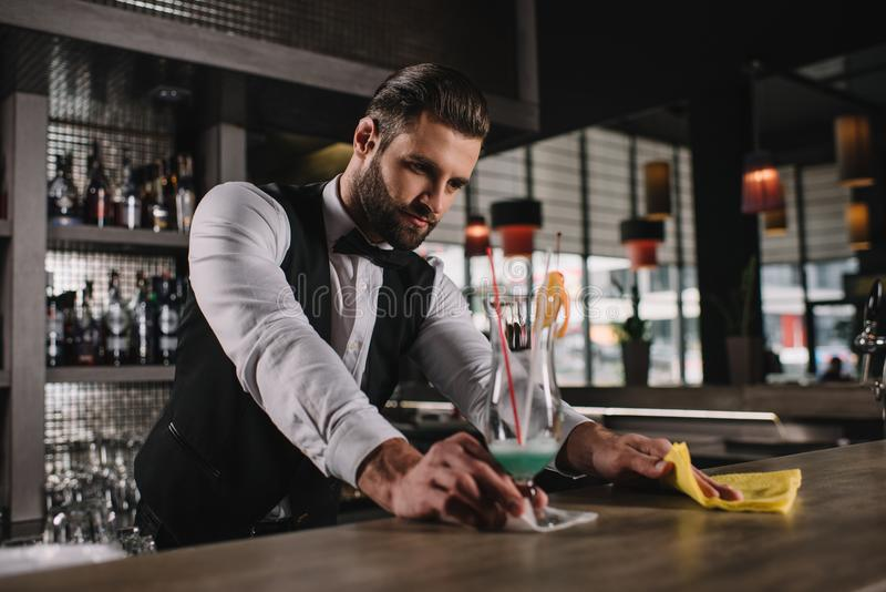 handsome bartender cleaning bar counter royalty free stock photo