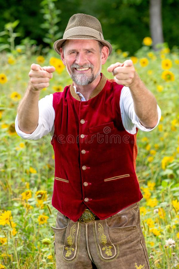 Handsome bavarian man in his 50s standing in garden with thumbs up stock photo