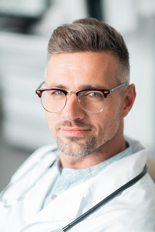 Handsome bearded blue-eyed plastic surgeon wearing glasses royalty free stock image