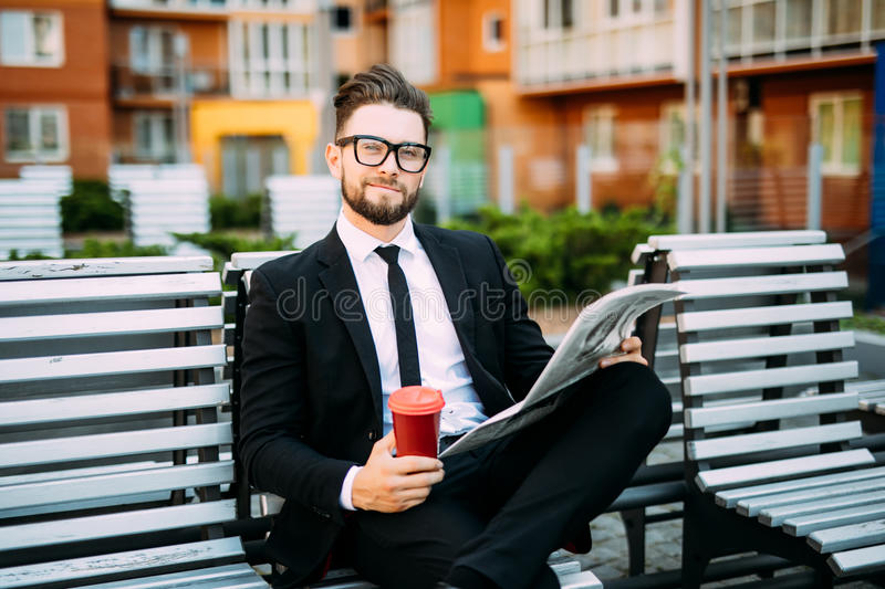 Handsome bearded businessman in classic suit is drinking coffee and reading a newspaper while resting on the bench in the city stock photo