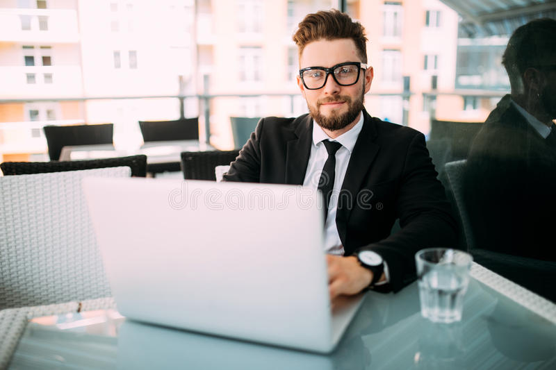 Handsome bearded businessman in classic suit is using a laptop and taking notes while sitting in cafe in the city stock images