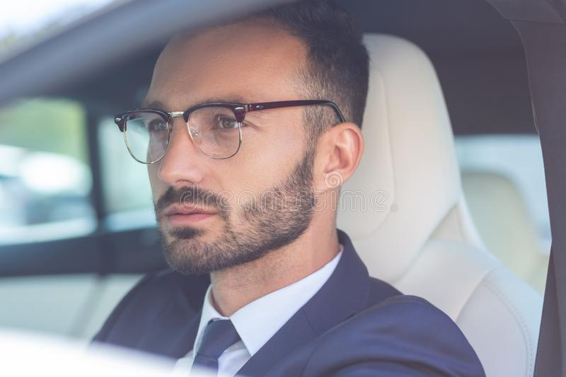 Handsome bearded businessman sitting in white car salon royalty free stock images