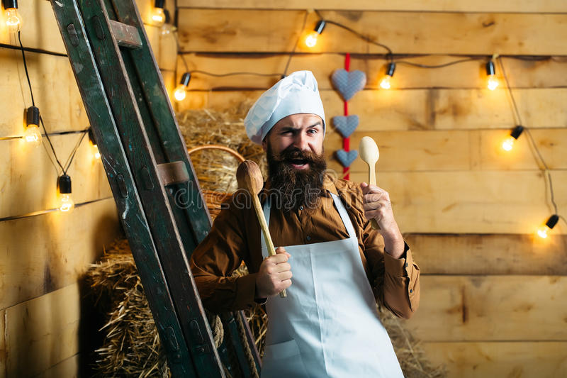 Handsome bearded chef cook. Handsome funny bearded cook chef in white uniform and hat with long lush moustache on smiling face holding wooden spoons in hands stock images