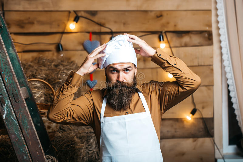 Handsome bearded chef cook. Handsome bearded cook chef in white uniform and hat with long lush moustache on serious face standing and putting hands on head near royalty free stock photography