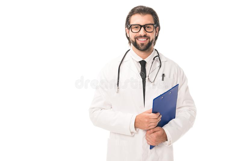 handsome bearded doctor in eyeglasses holding clipboard and smiling at camera royalty free stock images