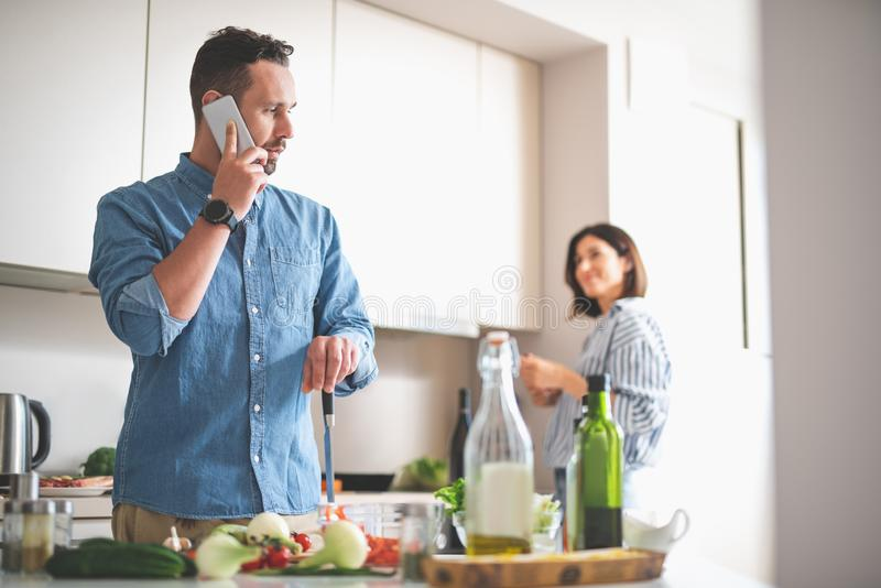 Handsome bearded gentleman talking on cellphone in kitchen stock photo