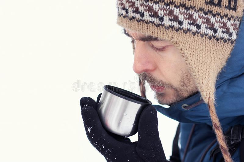 Handsome bearded hiker man in warm clothes drink tea in mug from thermos on white background. Season concept royalty free stock photography