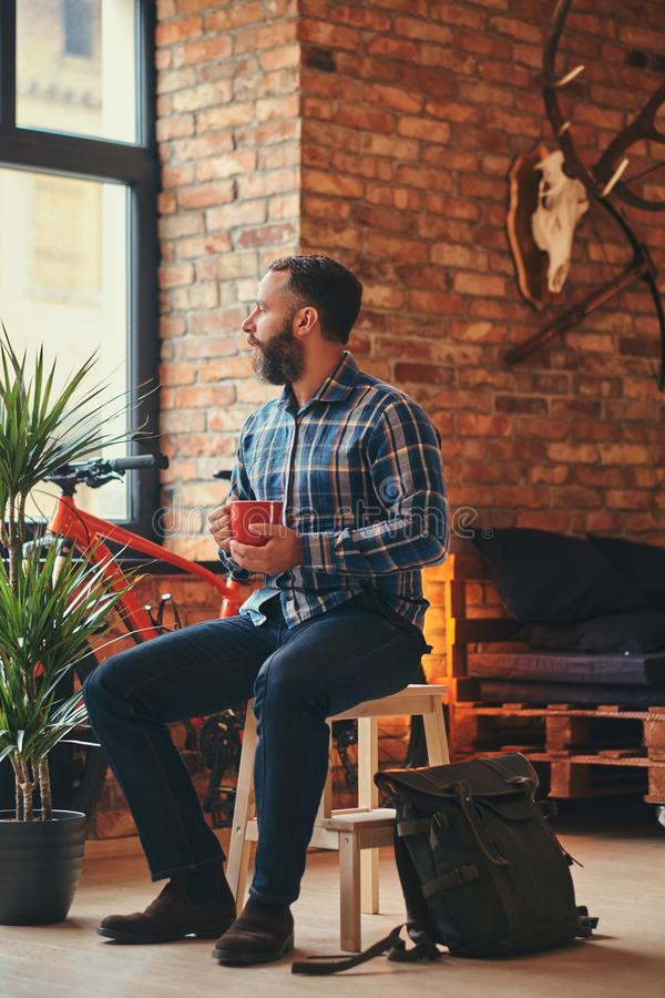 Handsome bearded hipster male in a blue fleece shirt and jeans holds a cup of morning coffee while sitting on a wooden royalty free stock image