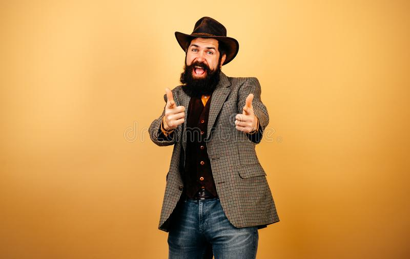 Handsome bearded hipster man in blazer and hat  at orange background. Gentleman in plaided jacket showing his royalty free stock photography
