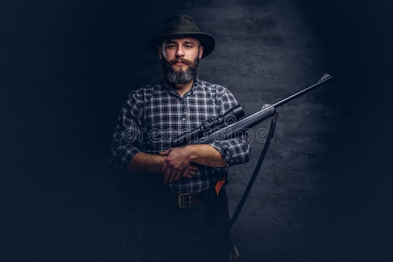Handsome bearded hunter traveler in a fleece shirt and hat holds rifle with a sight. royalty free stock photos
