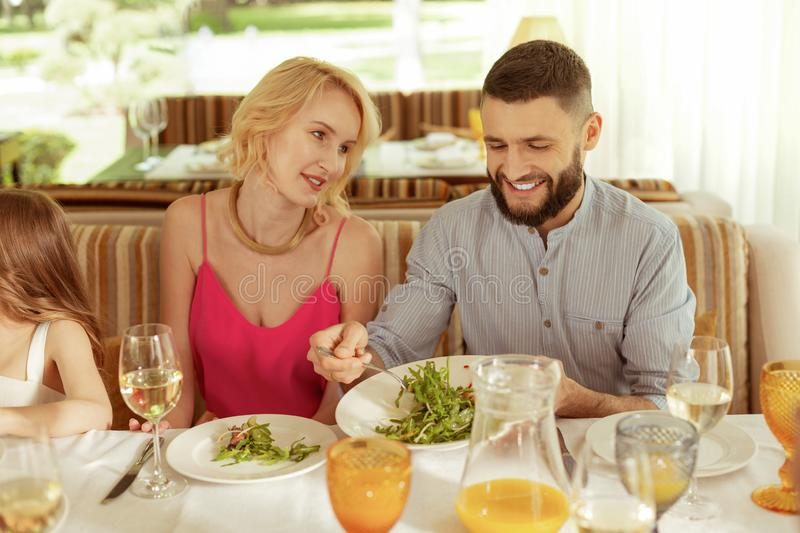 Handsome bearded husband treating his wife giving her some salad stock photography