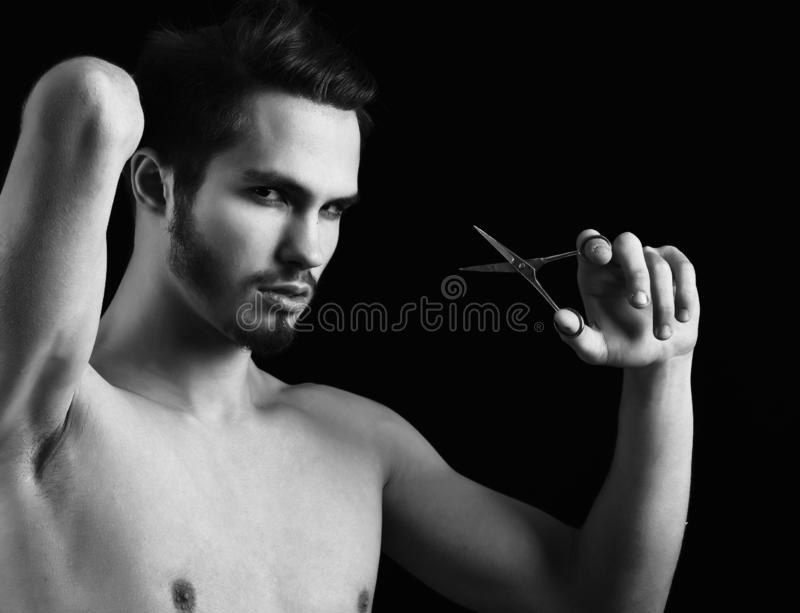 Handsome bearded macho man with stylish hair on serious face and naked chest holding scissors in studio on black stock photography