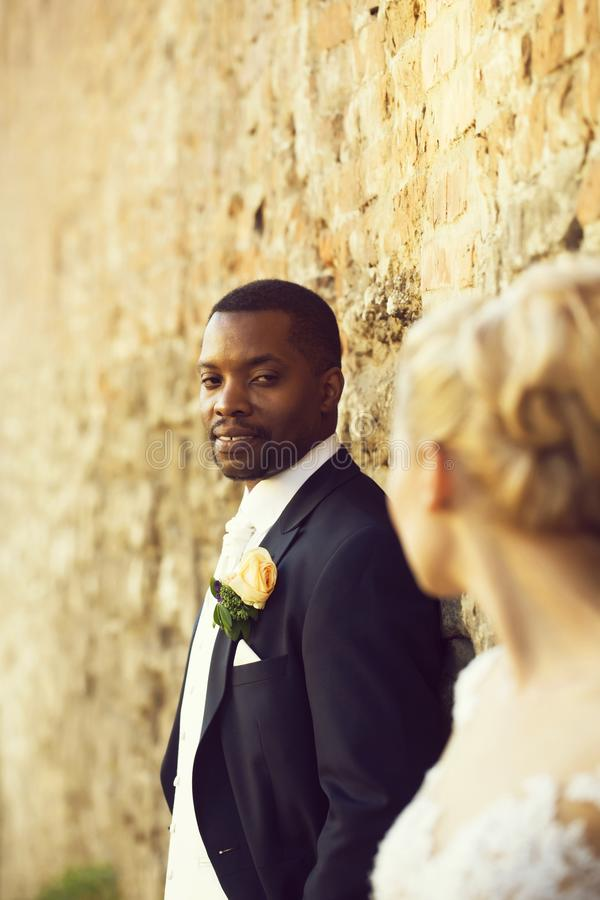 Handsome bearded man or african American groom. Handsome bearded men or african American groom in elegant suit coat with white tie and flower boutonniere for stock photo
