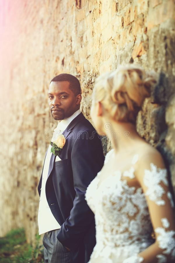 Handsome bearded man or african American groom. Handsome bearded men or african American groom in elegant suit coat with white tie and flower boutonniere for royalty free stock photos
