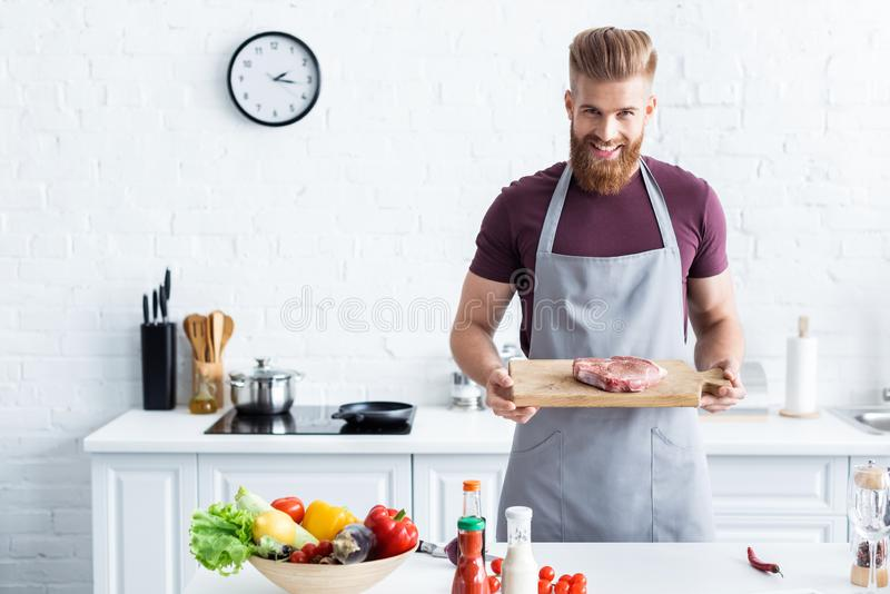 handsome bearded man in apron holding wooden cutting board with raw steak and smiling royalty free stock image