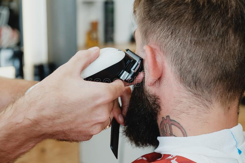 Handsome bearded man in barbershop. Barber cuts hair with elect stock photos